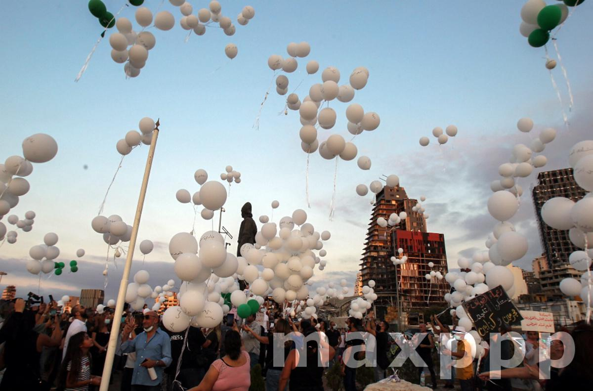 Anti-government protestors release balloons depicting the names of victims of Beirut blast