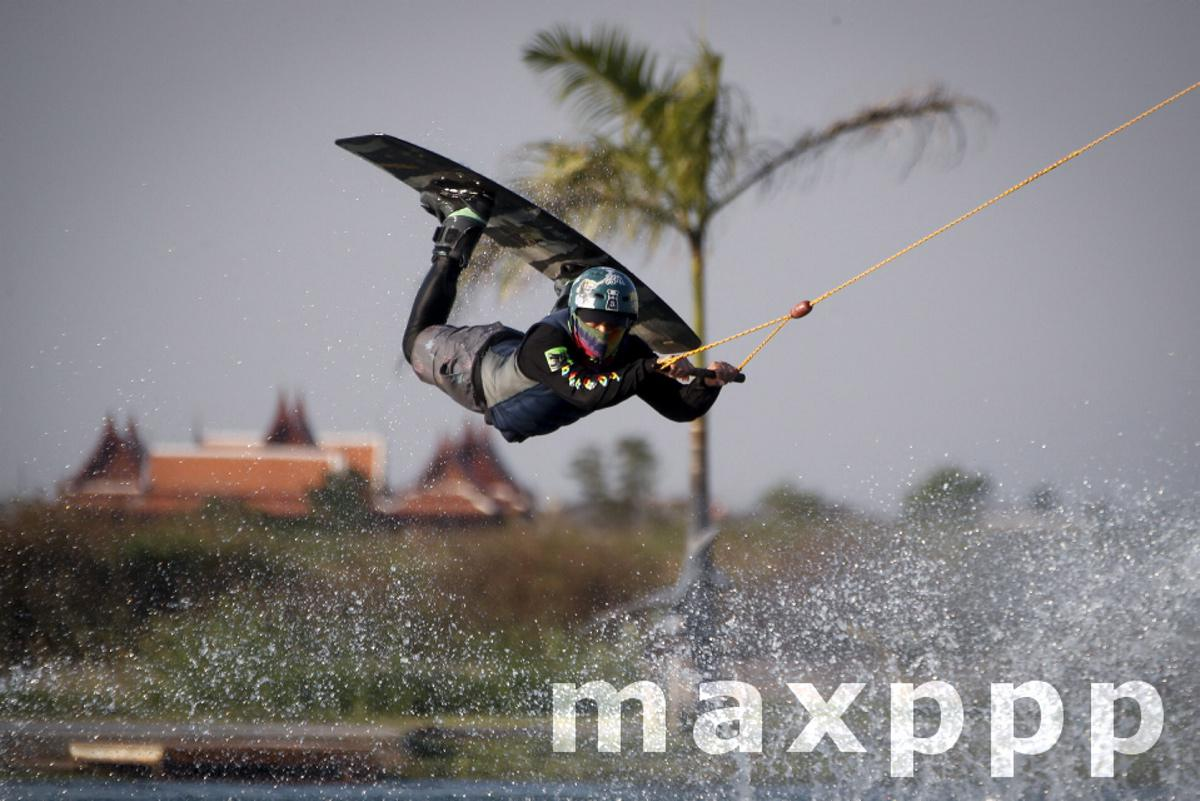 People wear protective face masks to enjoy a day at a wakeboard park in Thailand