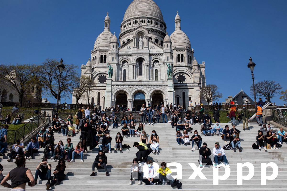 Parisians enjoy the good weather on the stairs of the Sacre Coeur Basilica